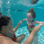 woman and holding girl's hands under water