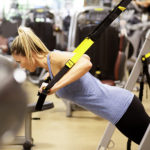 woman leaning forward on trx straps