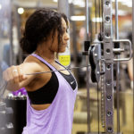 woman pulling out resistance bands on weight machine