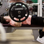 man on weight bench lifting barbell