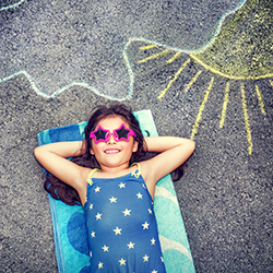 Happy little girl wearing swimsuit and stylish sunglasses lying down on the asphalt near picture of the sun comes out from behind the clouds
