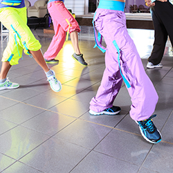 legs of people in zumba class lifting hip with colorful ribbons on their pants