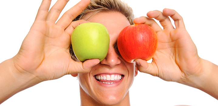 young man holding green and red apples in front of eyes