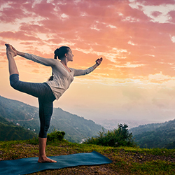woman doing dancers pose overlooking mountain landscape