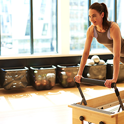 woman standing on pilates reformer